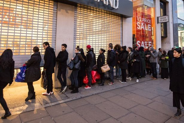 A queue of shoppers waiting outside a large shop for it to open.