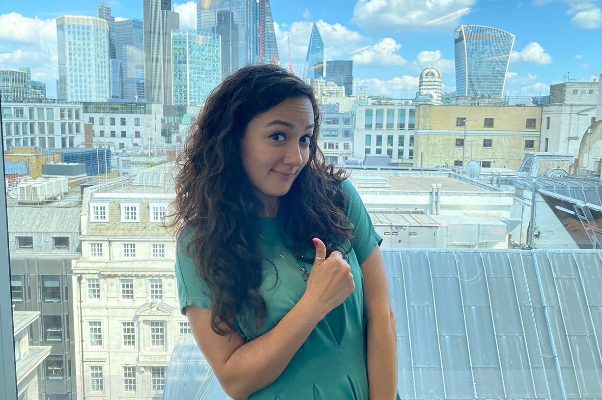 A picture of the author in front of a window, with a cityscape in the background. She is giving a thumbs up.